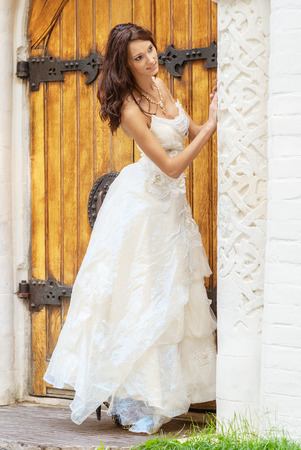 Young beautiful bride in white wedding dress standing about vintage wooden doors. photo