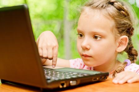 Little girl presses key on laptop Stock Photo - 29989503