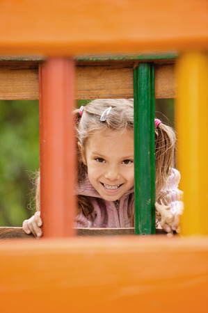 Beautiful joyful little girl on children's playground. Stock Photo - 29989505