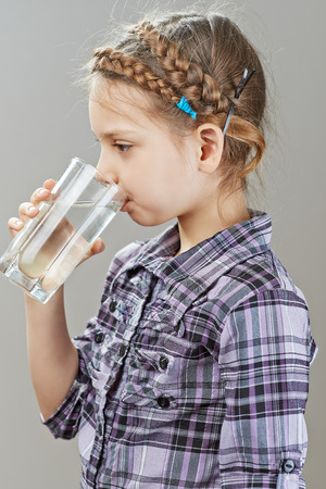 Beautiful little girl is drinking water, on gray background. Stock Photo - 29989511
