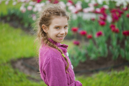 Portrait of pretty little girl in blue jacket in tulip park. Stock Photo - 29989515