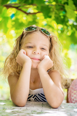 Portrait of beautiful smiling little girl with sunglasses in green summer city park. photo