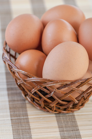 viands: Wicker basket with chicken eggs on table with striped tablecloth.