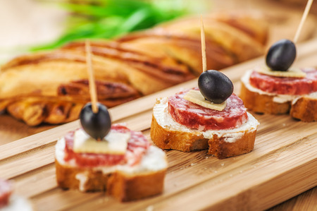 toothpick: Sausage sandwiches, cheese and olives on toothpick, wooden table in background.