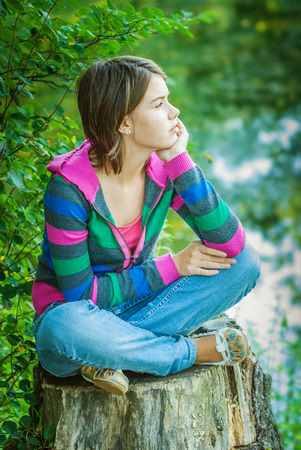 Girl-teenager in striped jacket with hood sits on big stub which is on bank of lake. photo