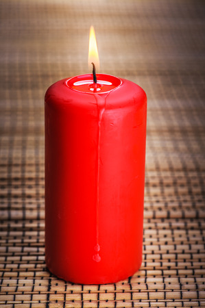 Red burning candle standing on wooden table. photo