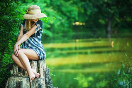pies sexis: Sonrisas de joven en el sombrero de paja de código auxiliar, en el Parque de la ciudad de verano.