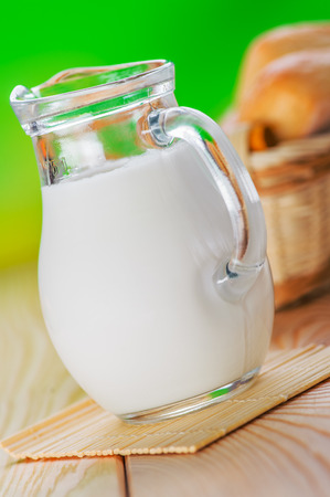 on wooden table pone bun, pitcher of milk,on green background photo
