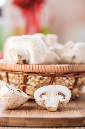 Champignon mushrooms with white variety on wooden table in basket. photo