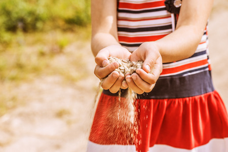 child's: Little girl throws sand from palms. Stock Photo
