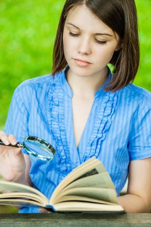 Portrait young woman short hair close-up reading book magnifier at summer green park photo