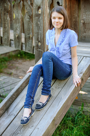 moccasins: Young beautiful dark-haired smiling woman wearing blue blouse and jeans sitting on wooden staircase at summer park.