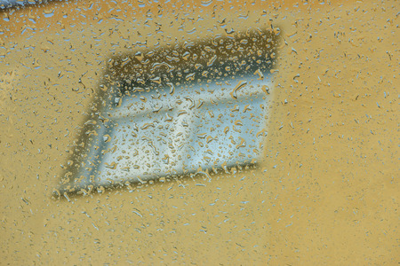 sliding colors: Raindrops on window with view on yellow wall with another window. Stock Photo