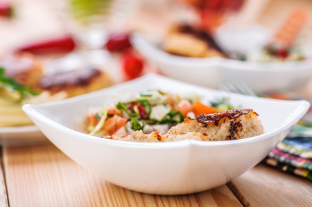 chicken salad: abundance of food on kitchen wooden table on napkin and fork with bowl of salad (radishes, tomatoes, parsley, eggs), meat katlety (pork, beef, lamb)