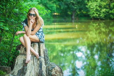 sexy füsse: Junge Frau lächelt in den schwarzen Gläsern auf Stub, im Sommer Stadtpark.