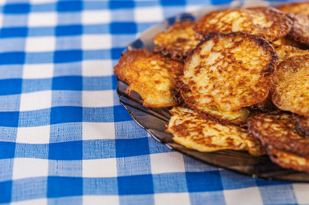 viands: Plate with vegetable fritters on table with blue checkered tablecloth.