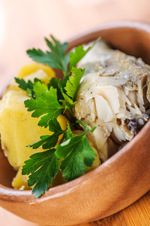 hake: Fish with boiled potatoes and parsley in a bowl on wooden table Stock Photo
