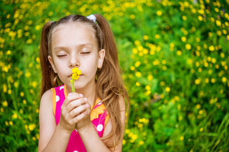 Little girl in yellow dress smells chamomile on green meadow. photo