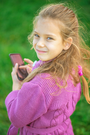 tresses: Beautiful little girl writes stylus on device, against summer green of park.
