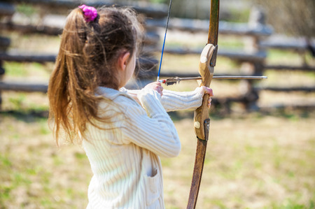 Beautiful little girl shoots bow at entertainment park. photo