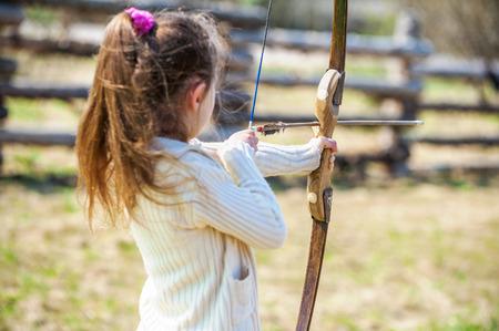 archery: Beautiful little girl shoots bow at entertainment park.
