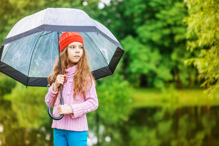 Little beautiful pensive girl in red cap and an umbrella on background of autumn park with lake. photo