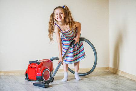hoover: Little beautiful smiling girl running with vacuum cleaner at home. Stock Photo