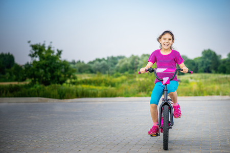 kids playing outside: Smiling little girl riding bicycle in city park. Stock Photo