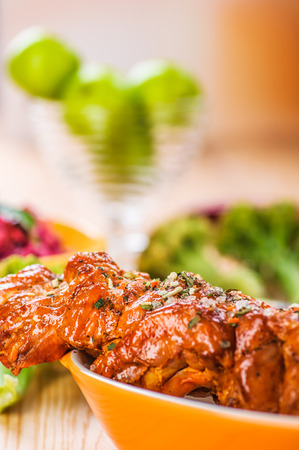 mouthwatering: against the background of the wooden kitchen table on checkered cloth, mouth-watering meat kebab (pork, beef, lamb, chicken) on skewer in large bowl Stock Photo