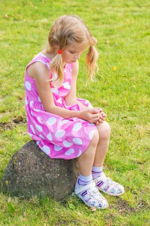 Little sad beautiful girl sitting on stone in summer city park.