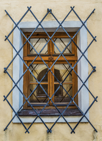 castings: Window on an old European building with wrought iron bars.