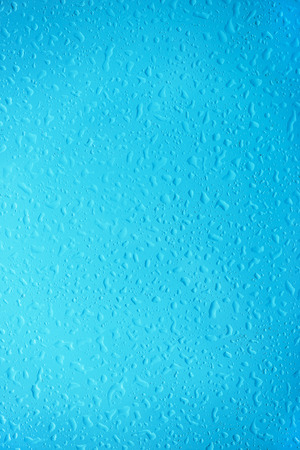 texture: Raindrops on window with view of overcast sky.