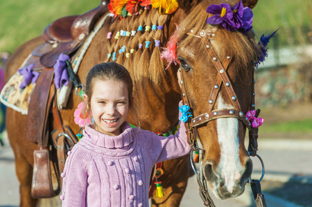 summer activities: Little girl with festive horse in summer city Park.