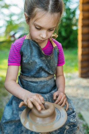 sculptor: Little girl produced on potters wheel pot. Stock Photo