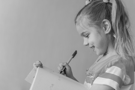 Beautiful smling little girl writes pen in notebook. Black-and-white photo. photo