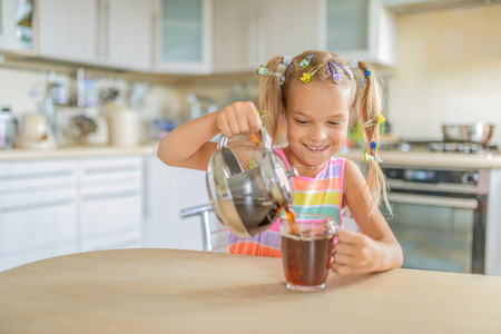 Little beautiful smiling girl pours tea from teapot into cup at kitchen table. photo