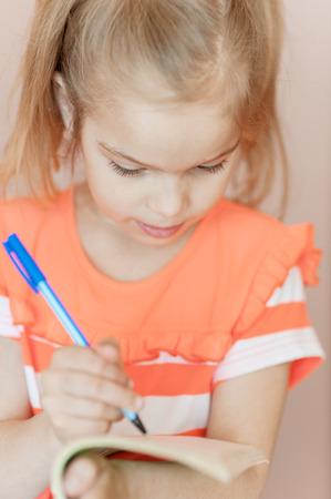 Beautiful little girl writes pen in notebook. photo
