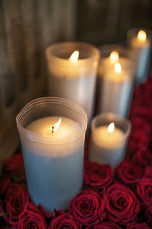 bougie coeur: Bougies dans des gobelets en plastique entouré de roses rouges.
