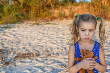 animal sad face: Little beautiful blonde sad girl holding teddy bear on sandy beach. Stock Photo