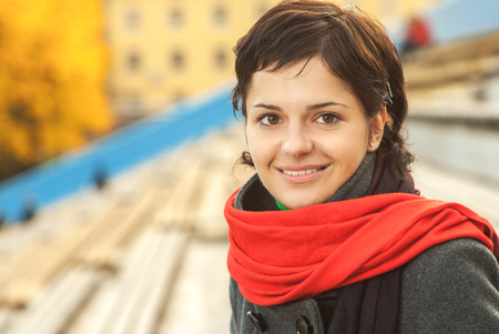Beautiful girl with red scarf on autumn background. photo