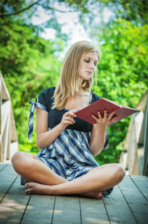 naturally: beautiful young woman reading book on green background Stock Photo