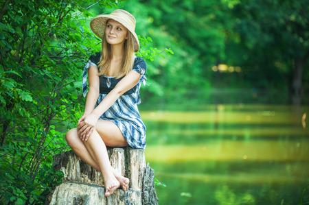 sexy füsse: Junge Frau lächelt in Strohhut auf Stub, im Sommer Stadtpark. Lizenzfreie Bilder