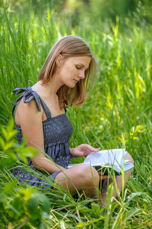 pleasure of reading: portrait of cute charming girl reading book in summer green forest