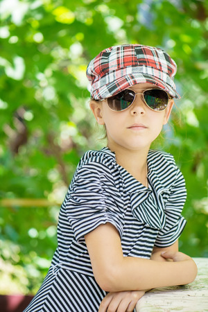 child in bed: Portrait of beautiful sad little girl with sunglasses in green summer city park. Stock Photo