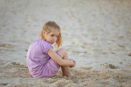 petite fille triste: Belle petite fille triste assis sur la plage de sable publique.