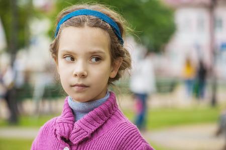 Portrait of beautiful little girl in purple sweater on background of autumn park. photo