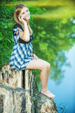 ravishing: Portrait of young attractive dark-haired woman wearing black dress, speaking on mobile phone, sitting on stump against lake at summer green park. Stock Photo