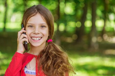 conversaciones: Ni�a hermosa en vestido rojo risas y habla por tel�fono m�vil, contra el Parque de verano de la ciudad. Foto de archivo