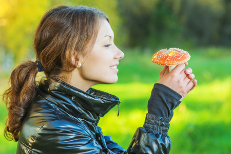 admires: Beautiful girl holds fly agaric in hand and admires it. Stock Photo