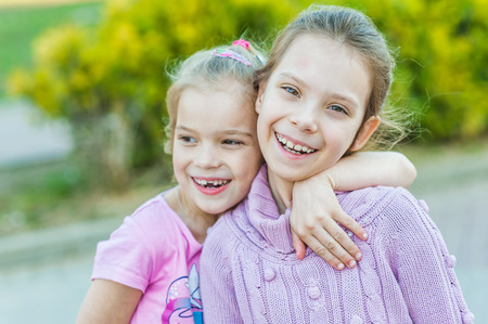 arms around: Two young sisters hugging, in summer city park.